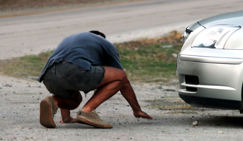 A man looks underneath his car which has broken down