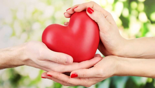 Two pairs of hands holding a heart