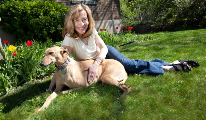 A woman resting with her pet dog on grass