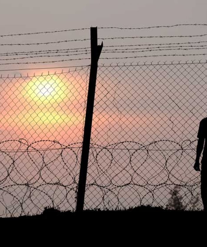 The sun sets behind a barbed wire fence