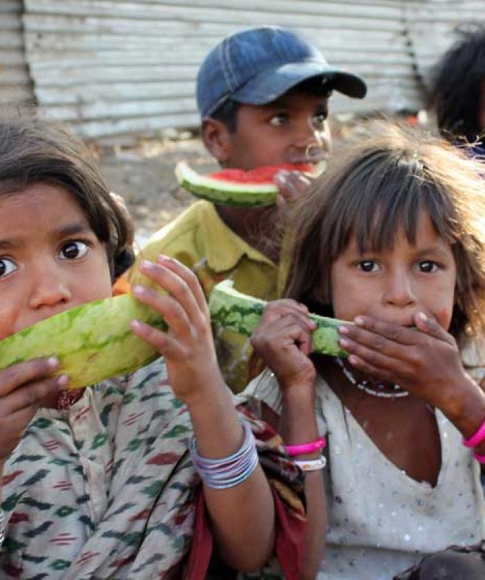 Poor children eating watermelon